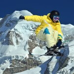 A young freerider jumping with high mountains and glaciers behind