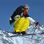 Freeride ski jumper in a crouch position high above the ground. Snow covered mountains in the background